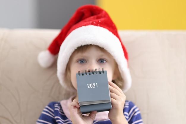 Little girl in santa claus hat holds table calendar for 2021