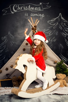 Little girl in santa costume on a rocking horse is ready to celebrate the holidays.