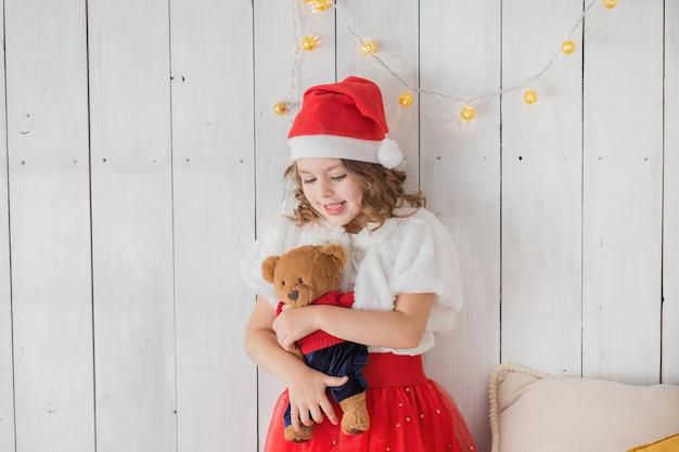 Little girl in santa costume with teddy bear indoor