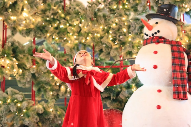 Little girl in santa dress has fun with snow on winter time.