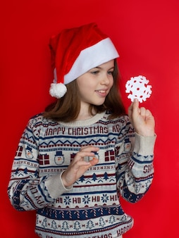 Little girl in santa hat holding a snowflake new year and christmas concept