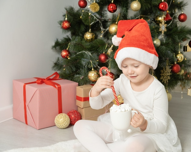 Little girl in santa hat holds a cup of hot chocolate or cocoa with marshmallow near christmas tree.