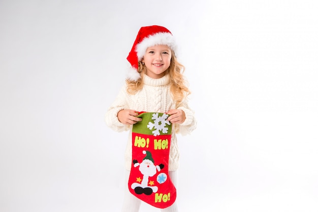 Little girl in a santa hat is holding a christmas sock