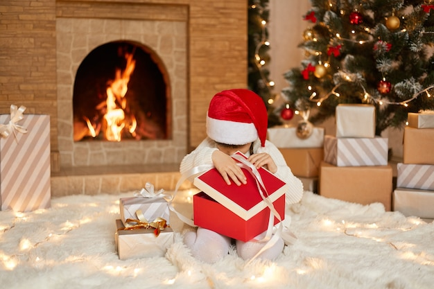 Little girl in santa hat opening gift box, looking inside it, wearing white jumper and red santa claus hat, sitting on floor in festive living room, posing with fireplace and xmas tree.