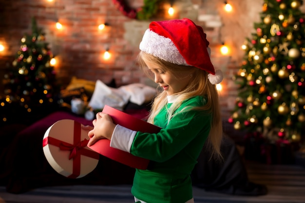 Little girl in santa hat opens a gift box