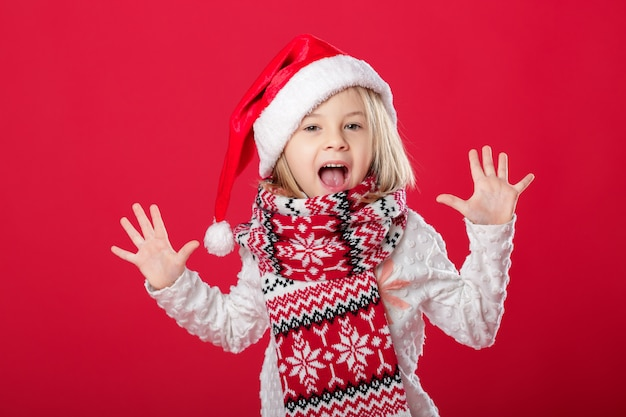 Little girl in santa hat and scarf on red