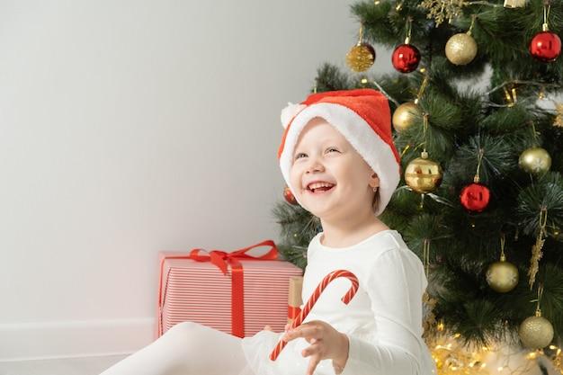 Little girl in santa hat with christmas lollipop near christmas tree.