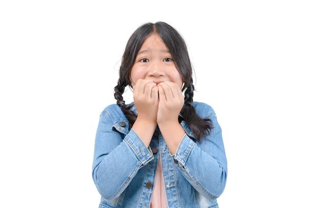 어린 소녀는 흰색으로 격리된 눈을 크게 뜨고 카메라를 바라보며 손가락 손톱을 물어뜯고 두려워하고 불안해합니다. 얼굴 감정