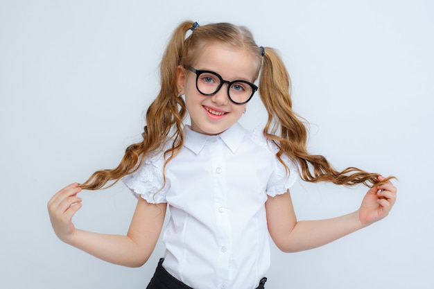 A little girl in school uniform and glasses on a white background