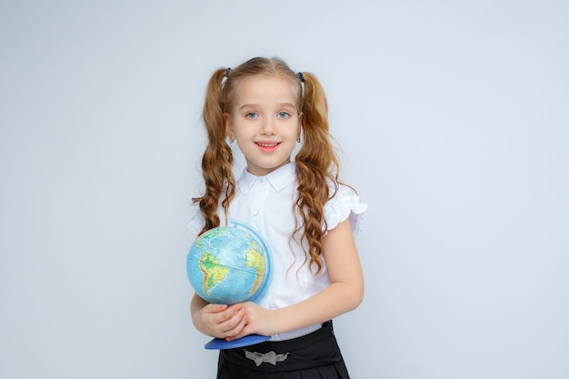 A little girl in school uniform  holds a globe in her hands on a white background