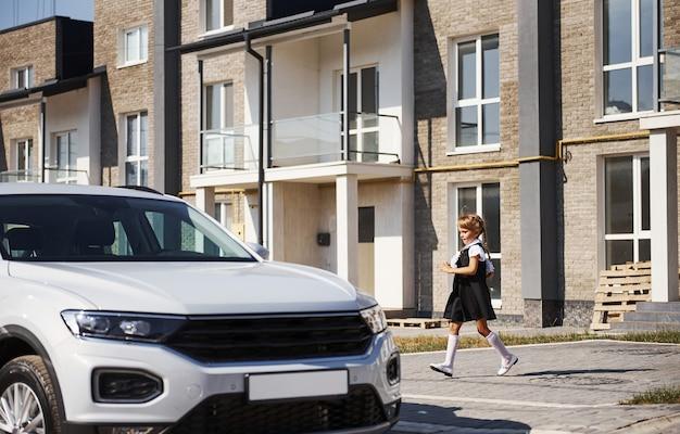 Little girl in school uniform runs ro a modern white car outdoors on the street.