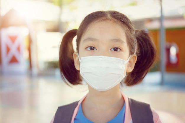 Little girl in school uniform wearing a surgical mask with blurred background