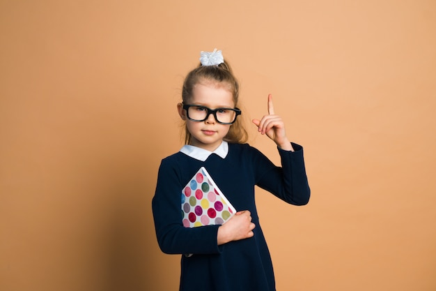 Little girl in school uniform with book on color background, holding hand, have idea