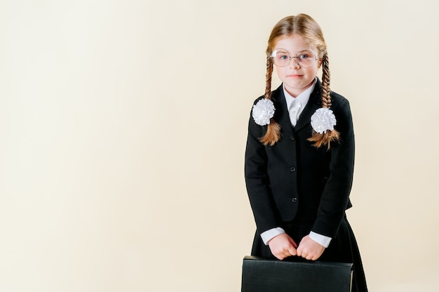 A little girl in a school uniform with pigtails holding a briefcase