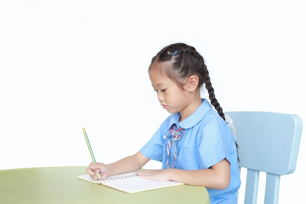Little girl in school uniform writing on book at desk on white background