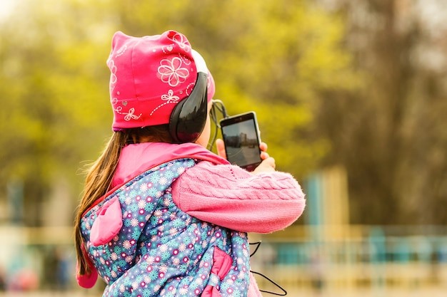Little girl schoolgirl. summer in nature. in hands holding a smartphone listening to music on headphones. take a picture on phone, talking on the video call. emotion smiles happily.