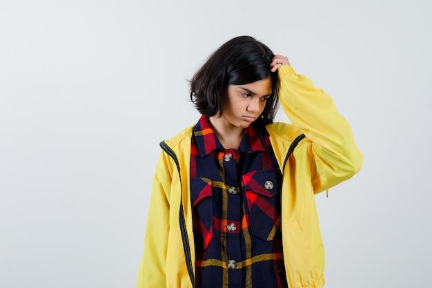 Bambina che gratta la testa in camicia a quadri, giacca e guardando premurosa, vista frontale.