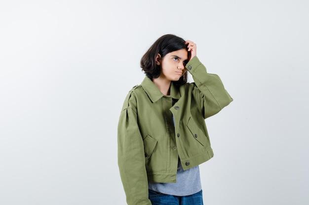 Bambina che graffia la testa in cappotto, t-shirt, jeans e sembra esitante, vista frontale.