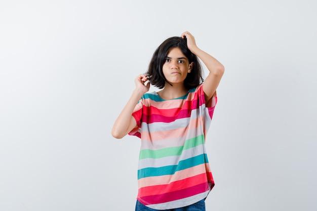 小さな女の子がtシャツで頭をかいて、思慮深く、正面図を探しています。