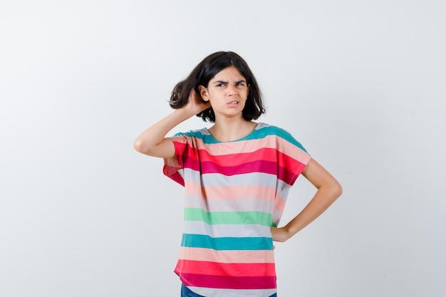 Bambina che gratta la testa in maglietta e sembra smemorata. vista frontale.