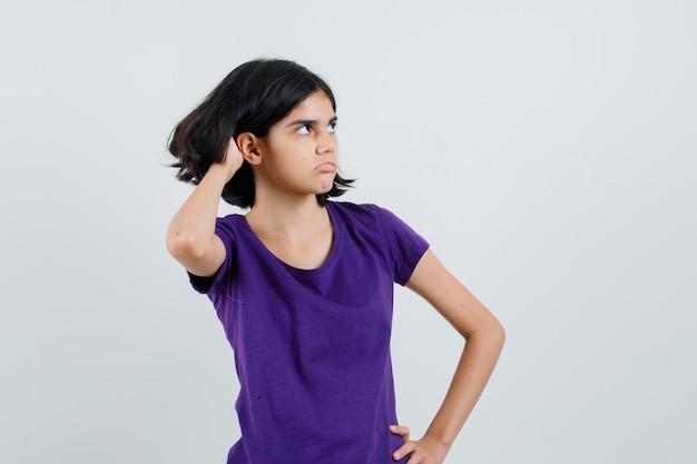 Bambina che graffia la testa in maglietta e che sembra esitante