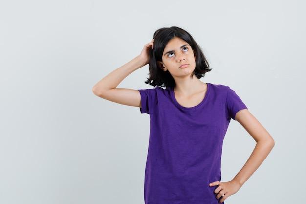 Bambina che graffia la testa in maglietta e sembra indecisa