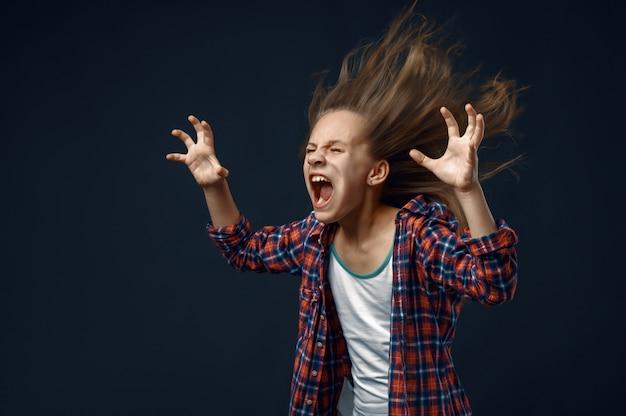 Маленькая девочка кричит в студии, развивая эффект прически. дети и ветер, ребенок, изолированные на темном фоне, эмоции ребенка