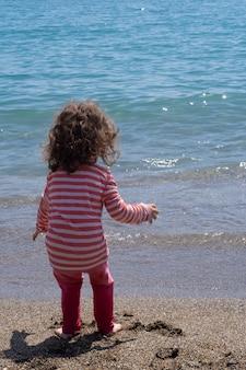 Маленькая девочка, впервые увидевшая море босиком