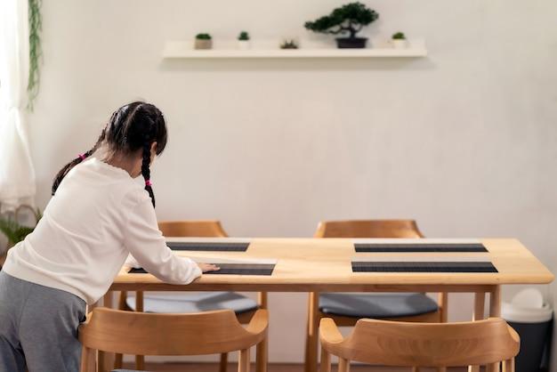 Маленькая девочка настраивает обеденный стол перед едой.