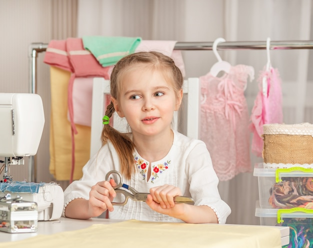Little girl in a sewing workshop