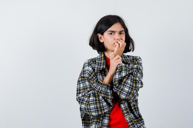 Bambina in camicia, giacca che tiene la mano sulla bocca e sembra pensierosa, vista frontale.