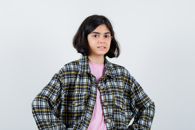 Little girl in shirt,jacket looking at camera and looking focused , front view.