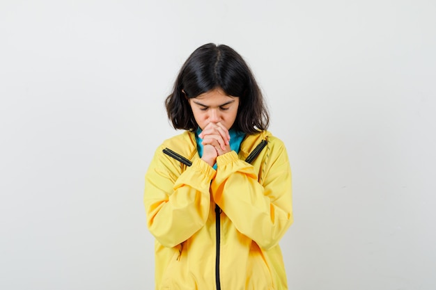 Little girl in shirt, jacket showing clasped hands in pleading gesture and looking hopeful , front view.