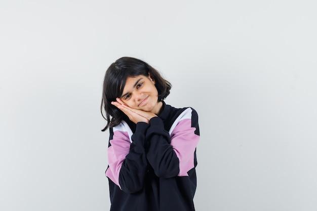 Bambina in camicia che si appoggia sulle palme come cuscino e che sembra incantevole, vista frontale.