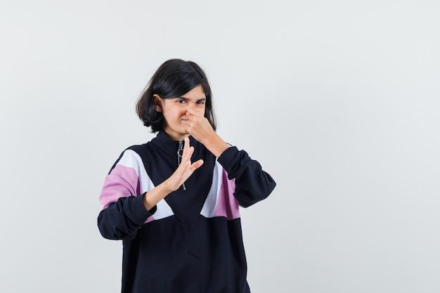 Bambina in camicia che pizzica il naso a causa del cattivo odore e sembra disgustato, vista frontale.