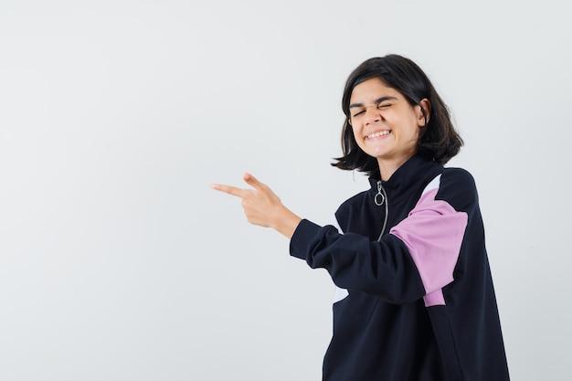Bambina in camicia che indica da parte e che sembra felice, vista frontale.