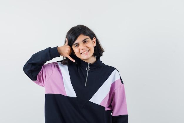 Bambina in camicia che mostra il gesto del telefono e che sembra allegro, vista frontale.
