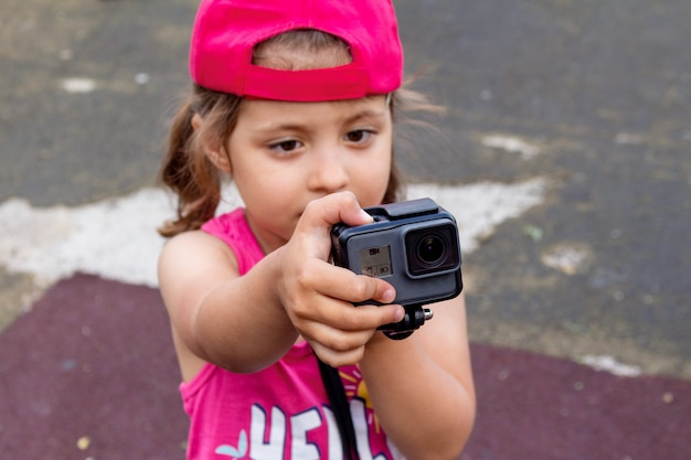 Little girl shooting blog on an action camera close up.