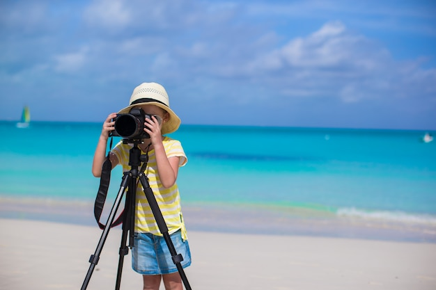 Little girl shooting with camera on tripod during her summer vacation