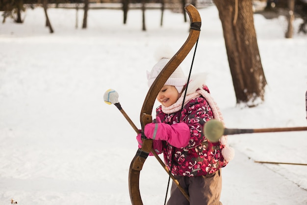 Little girl shoots a bow in winter