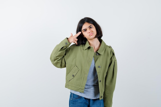Little girl shouting herself with hand gun in coat, t-shirt, jeans and looking sorrowful. front view.