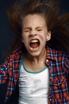 Маленькая девочка кричит в студии, развивая волосы