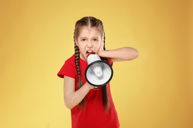 Little girl shouting into megaphone on color