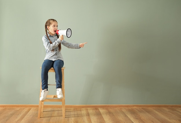 Little girl shouting into megaphone while sitting on chair against color wall