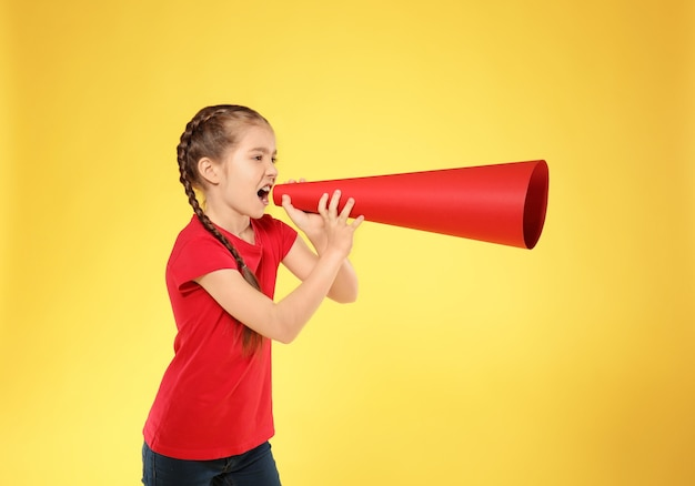 Little girl shouting into paper megaphone on color
