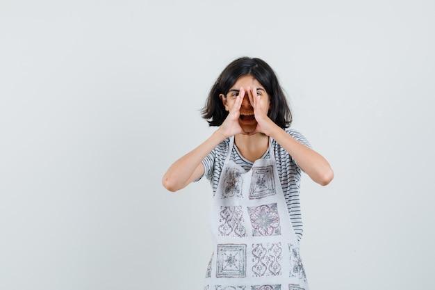 Bambina che grida o dice il segreto in maglietta, grembiule e sembra felice