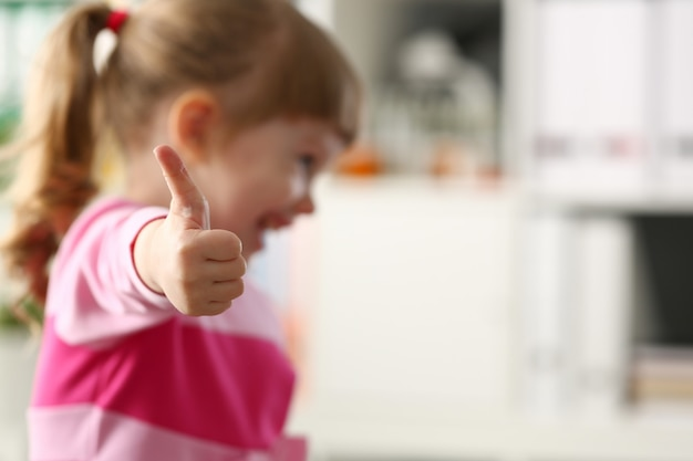 小さな女の子は彼女の腕で承認またはokサインを表示します