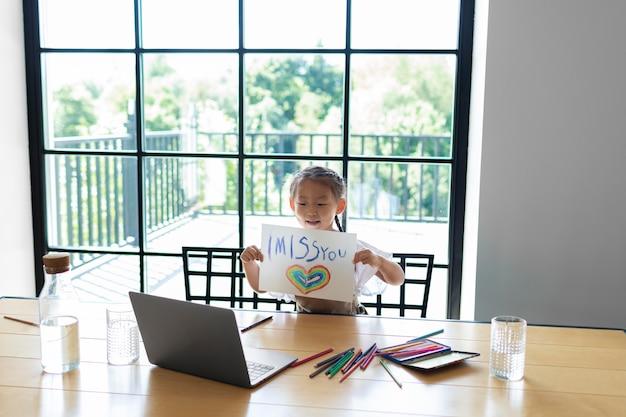 화상 통화로 가족에게 그림을 보여주는 어린 소녀