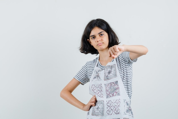 Little girl showing clenched fist in t-shirt, apron and looking confident