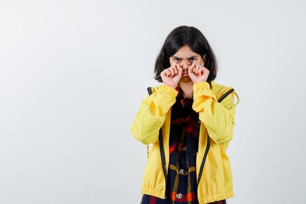 チェックのシャツ、ジャケットを着て、物欲しそうに見える手で泣くジェスチャーを示す少女